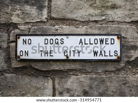 A plaque on the historic York City Walls detailing the fact that Dogs are not allowed.