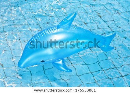 A plastic blue whale floating in a pool. - stock photo
