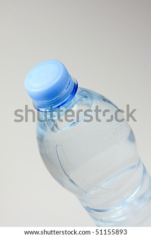 A plastic bottle filled with still water. Image isolated on white studio background. - stock photo