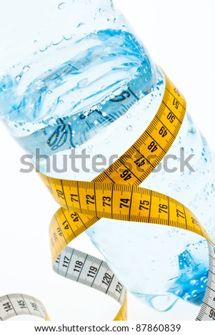 a plastic bottle of mineral water and measuring tape. symbol for diet. - stock photo