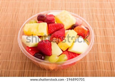 A plastic bowl of fresh cut fruit - stock photo