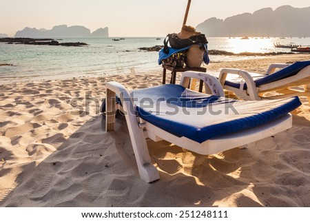 a plastic chaise lounge on a tropical beach on sunset in Phi Phi Island, Thailand - stock photo