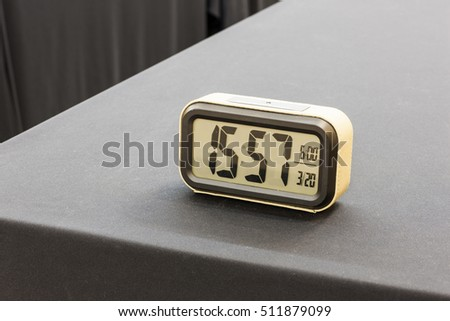 A plastic digital watch on the black table(desk) at the hotel, seoul.