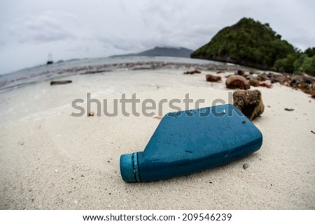 A plastic oil bottle and other pieces of garbage have washed up on a remote beach in Indonesia. This island is rarely visited yet has lots of trash as currents continually sweep plastic ashore. - stock photo