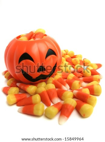 A plastic pumpkin filled with candy corn. - stock photo