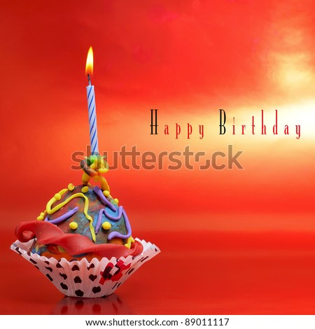 a plasticine cupcake with a candle on a red background with sentence happy birthday - stock photo