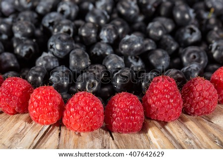 A plate full of fresh picked healthy blueberries with raspberry - stock photo