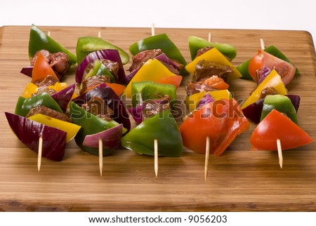 A plate full of fresh vegatables and meat for kabobs. - stock photo