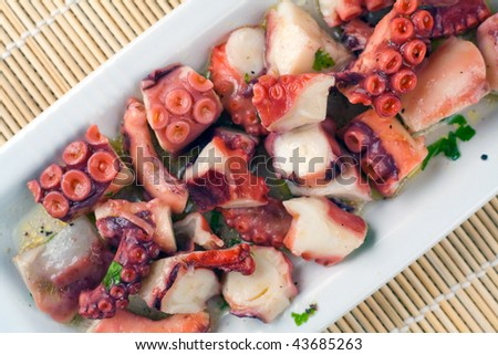 a plate full of octopus in a salad of lemon, olive oil and parsley