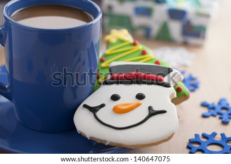 A plate of a blue mug with coffee and a smiling snowman cookie on the side - stock photo