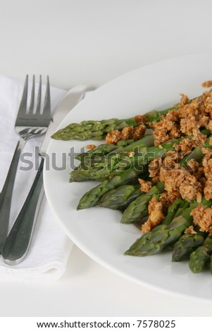 A plate of asparagus with thick satay sauce