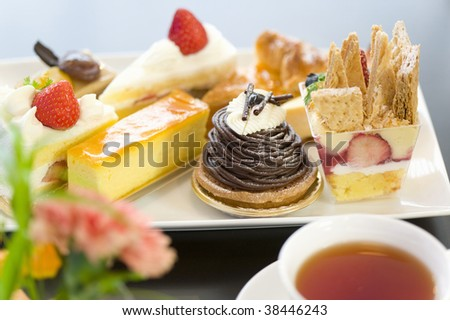 A plate of assorted cake with tea