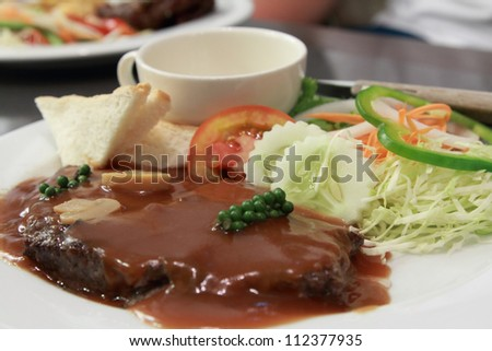 a plate of beef steak with pepper gravy - stock photo
