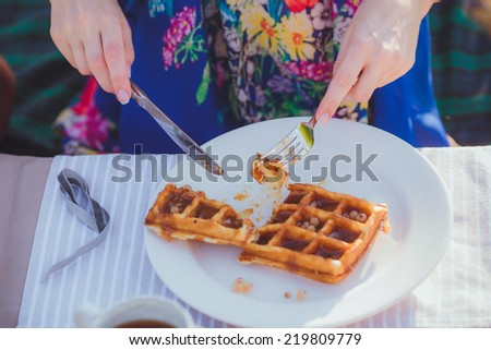 A plate of belgian waffles with fruit. Girl hands  preparing to eat it with knife, fork. - stock photo