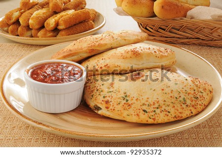 A plate of calzones with cheese and bread sticks - stock photo