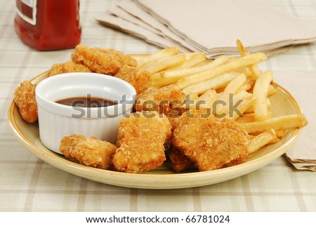 A plate of chicken nuggets with french fries - stock photo