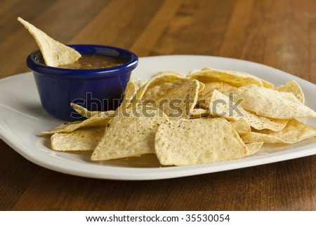 A plate of chips with salsa in a bowl - stock photo