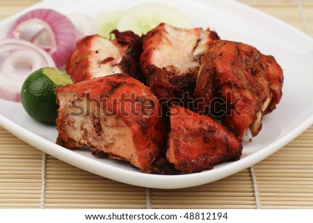 A plate of chopped Tandoori Chicken with some garnishing on a bamboo mat - stock photo