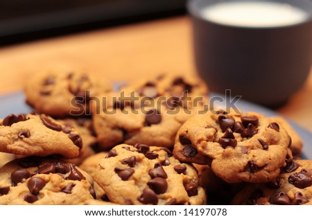 A plate of cookies with a cup of milk in the background - stock photo