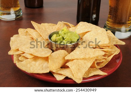 A plate of corn chips with guacamole and beer