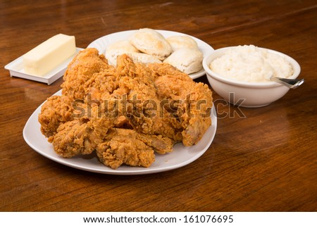 A plate of crispy fried chicken, a plate of biscuits, and a bowl of mashed potatoes - stock photo