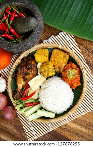 A Plate of Delicious Ayam Penyet with Sambal Belacan(Homemade Chili Sauce) and Tempe - local flavor - stock photo