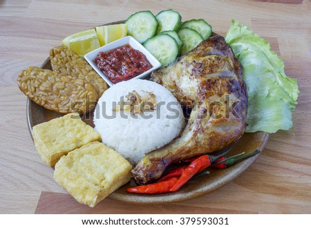 A Plate of Delicious Ayam Penyet with Sambal Belacan, Tempeh and Tofu, Famous  Indonesian Cuisine - stock photo