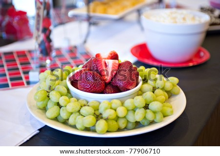 A plate of delicious grapes and strawberries
