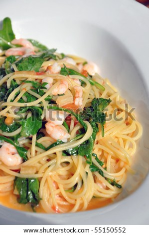 A plate of delicious italian pasta: spaghetti with shrimps and rucola. - stock photo