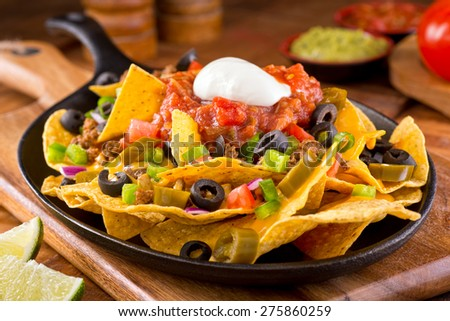 A plate of delicious tortilla nachos with melted cheese sauce, ground beef, jalapeno peppers, red onion, green onions, tomato, black olives, salsa, and sour cream with guacamole dip. - stock photo