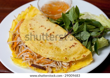 A plate of delicious Vietnamese pancake with loads of Vietnamese favourite herb--the basil leaves. - stock photo
