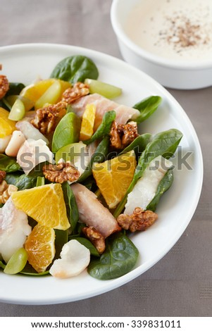 a plate of fish salad  with oranges and nuts - stock photo