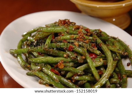 A plate of fresh-cut stir-fried green beans with a red chili sauce. There is a yellow bowl in the background. - stock photo
