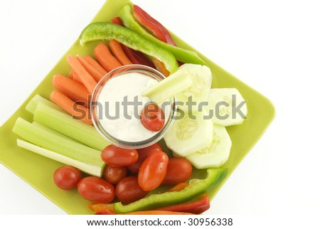 A plate of fresh cut vegetables with ranch dip on a plate isolated on white background with copy space - stock photo