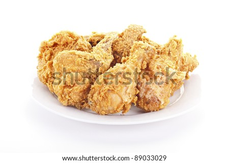 A plate of fresh, fried, crispy chicken on a white plate on a white table - stock photo