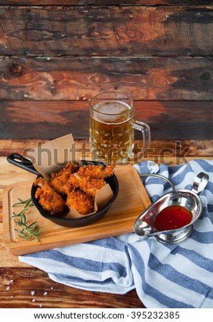 A plate of fresh, hot, crispy fried chicken with red sause on a blue plaid towel on a wood table. Snack to cold beer. - stock photo