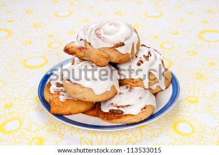 A plate of freshly baked cinnamon rolls with sugar icing dripping down the sides. - stock photo