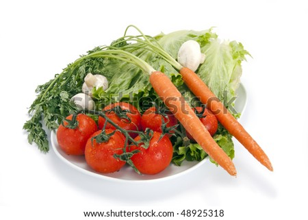A plate of freshly picked vegetables.  Included are vine ripened tomatoes, carrots, leaf lettuce, and mushrooms.