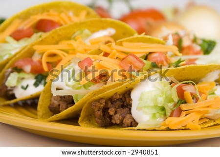 A plate of freshly prepared ground beef tacos, with tomato, freshly grated cheese, lettuce and sour cream.