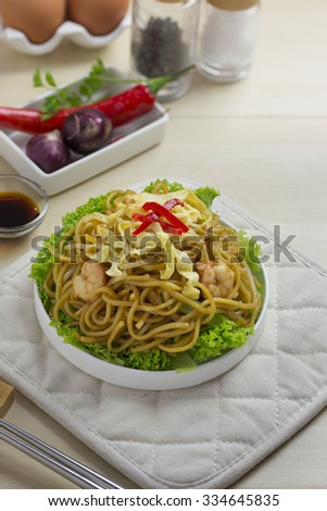A plate of fried seafood noodle on wooden background.