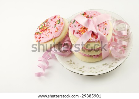 A plate of frosted pink sugar cookies with sprinkles in a stack tied with pink ribbon, isolated on white background with copy space - stock photo