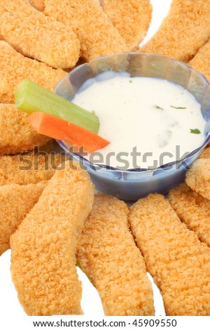 A plate of golden crispy chicken fingers with  vegetables and dip - stock photo