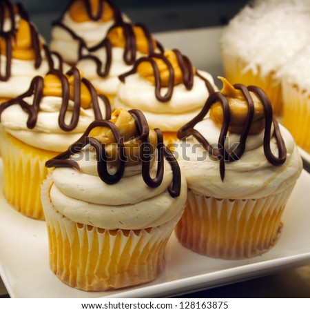 A plate of gorgeous yellow cupcakes decorated with frosting, peanut butter, and chocolate drizzle. - stock photo