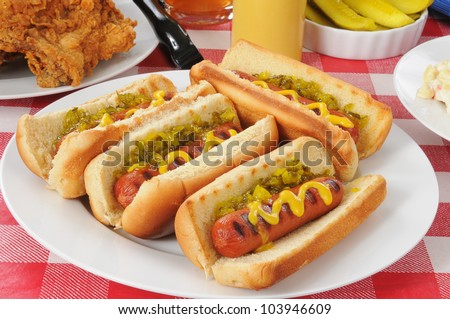 A plate of grilled hot dogs with mustard and relish on a picnic table - stock photo