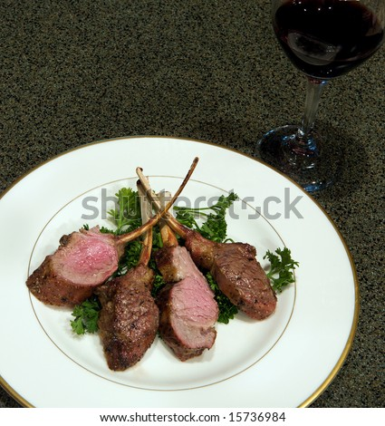 A plate of grilled Lamb Chops on a bed of fresh parsley with a glass of wine. - stock photo