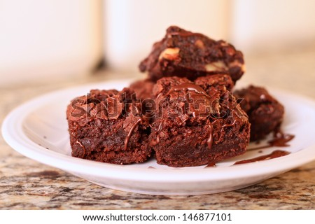 A plate of home made chocolate brownies, some with pecans, some without, covered in a chocolate drizzle. These brownies are completely vegan. - stock photo