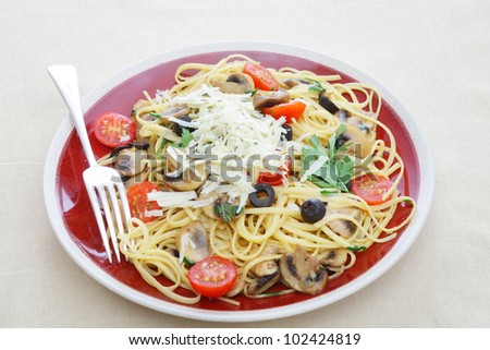 A plate of linguine tossed in a sauce of olive oil, mushrooms, garlic and basil, garnished with parsley, cherry tomatoes and sliced olives. - stock photo