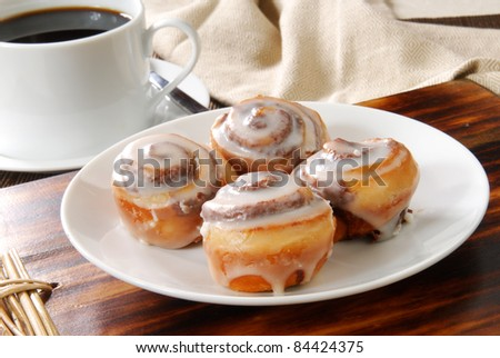 A plate of mini cinnamon rolls and a cup of black coffee - stock photo