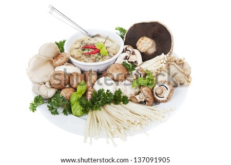 A plate of mixed mushrooms with a bowl of soup on a white background, main focus is on the soup.