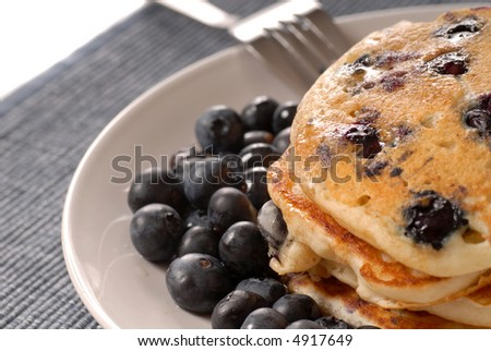 A plate of pancakes with fresh blueberries and syrup - stock photo